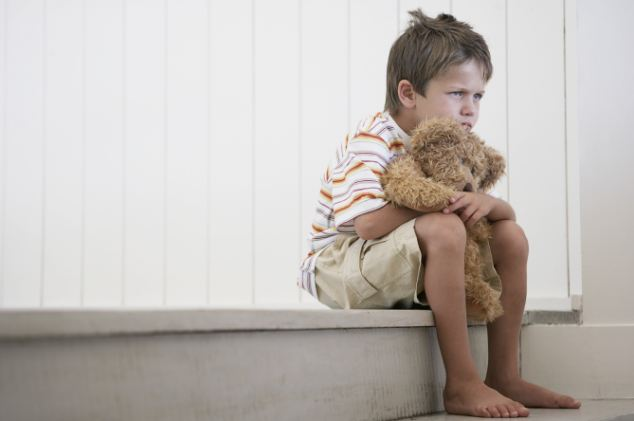 Sad young boy with a teddy bear --- Image by © Heide Benser/Corbis