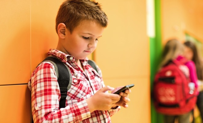 Elementary student standing in school hallway and text messaging on cell phone.