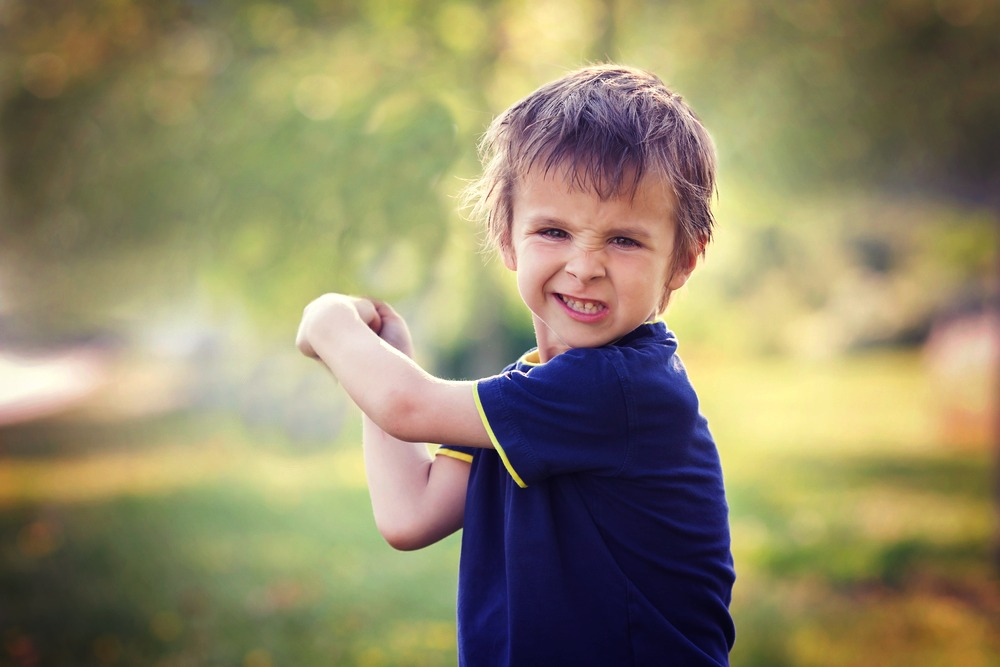 Angry little boy, holding sword, glaring with a mad face at the camera, outdoors in the park