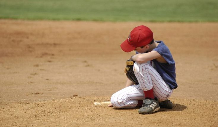 disappointed-boy-bending-down-on-baseball-field-135602649-571a51163df78c56400b61d3