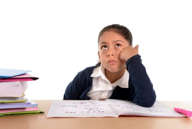 sweet little female latin child studying on desk looking bored and under stress thinking with a tired face expression in children education and back to school concept isolated on white background